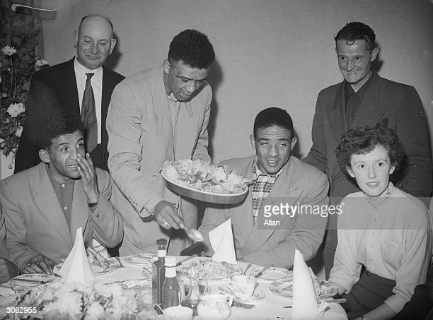 British middleweight boxer and European Champion Randolph Turpin eating with his brother Dick Turpin and family