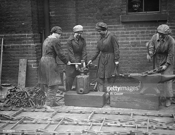 Women workers at the Gas Light and Coke Company at Bromley By Bow. Rivetting chains.