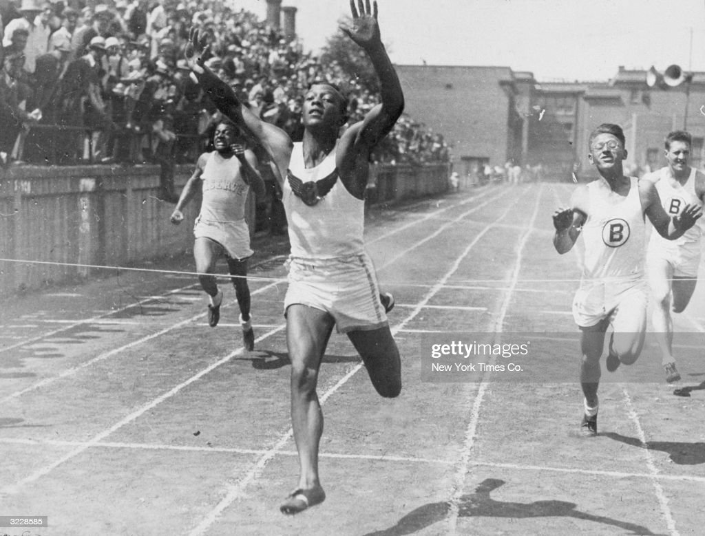 Cleveland high school student and future Olympic champion Jesse Owens (1913 - 1980) holds his hands in the air while crossing a finish line to break the world 100-meter record.