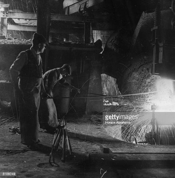 At a British steel foundry workers convert molten steel into hard ingots to be made into war weapons