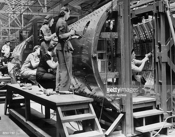 Female factory workers stand on wooden platforms as they rivet the outer shell of a bombbay section at Chrysler Corporation's DeSoto Bomber Plant