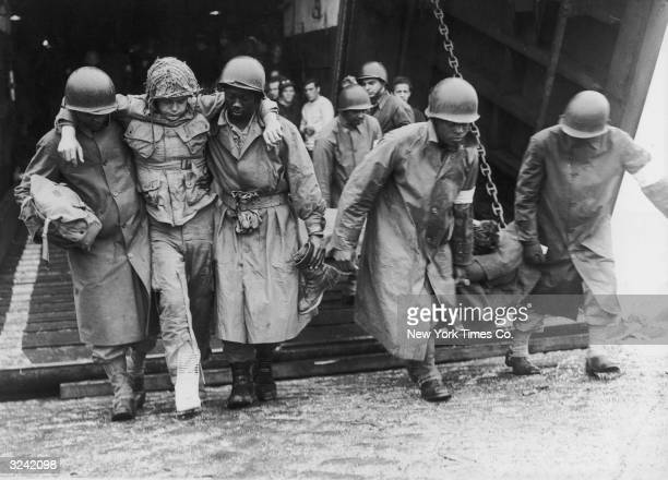Wounded American soldiers are helped ashore by Black soldiers at a British port, after arriving from France during World War II. The soldiers had...