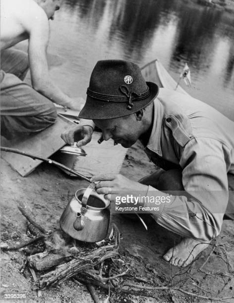 A Swedish hiker boiling a kettle over a fire for a coffee break during a midsummer hike