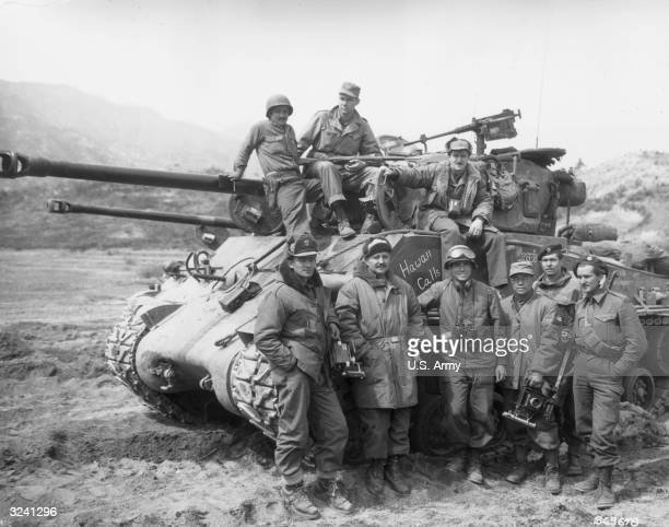 Group portrait of an American radiophoto crew posed on and around a tank with 'Hawaii Calls' written on the side during the Korean War Korea Several...