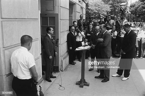 Segregationist Alabama Governor George C Wallace blocks the doorway to the University of Alabama while listening to Nicholas Katzenbach US Deputy...