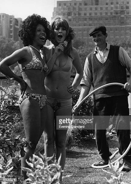 Two women modelling swimwear in a garden on London's South Bank watched by a gardener with a hose