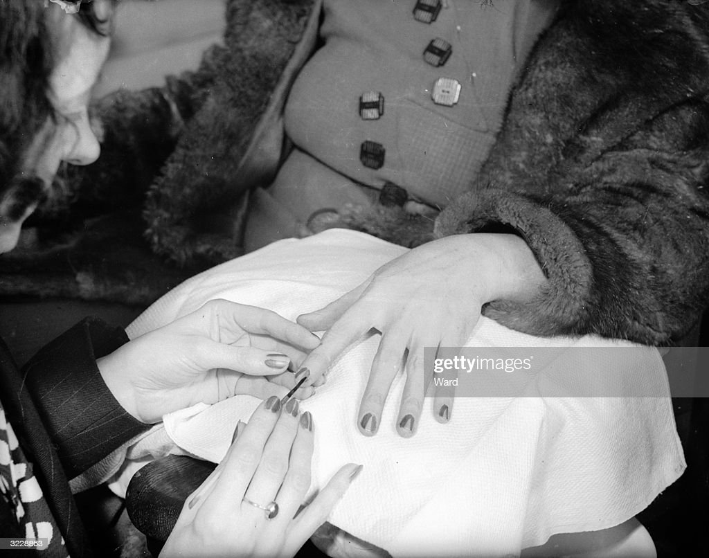 A woman at a beauty parlour in London having a commemorative design in red, white and blue, surmounted by a gold crown, stencilled onto her nails to mark the coronation of George VI.