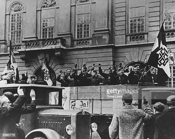 A truckload of cheering young Austrian patriots displaying flags of Schuschnigg Austria in front of the Austrian Foreign Office on Bellhaus Square...