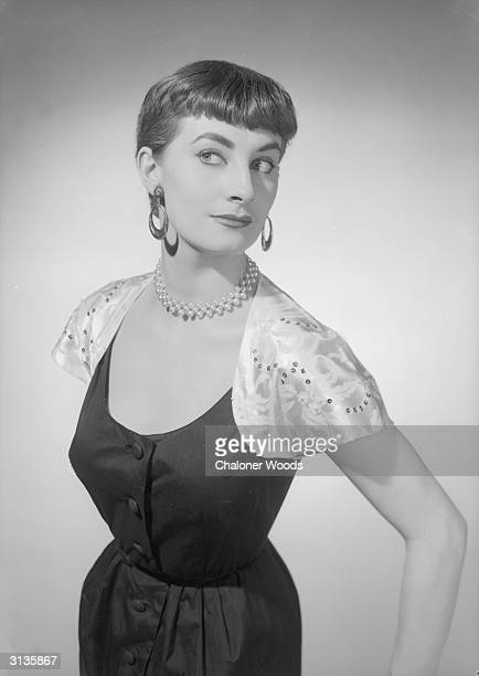 A woman with an Audrey Hepburn haircut modelling a black dress with white cape shoulders