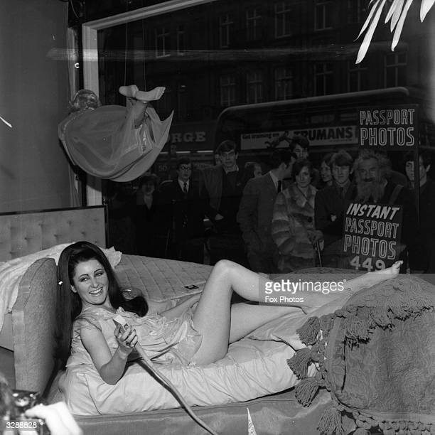 Model demonstrating a new electric bed by Sleepeezee in the window of Selfridges department store, Oxford St, London. The bed adjusts to any position...