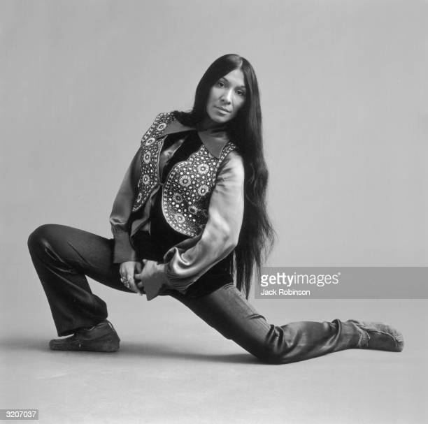 Fulllength portrait of Canadian musician Buffy St Marie kneeling on the floor with her hands clasped Her long black hair is down and she wears black...