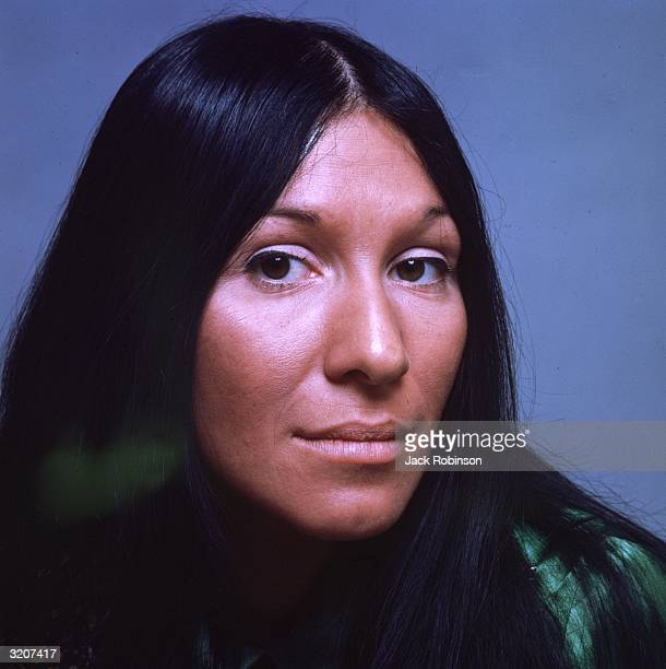 Headshot studio portrait of Canadian musician Buffy St Marie wearing her long hair parted in the center