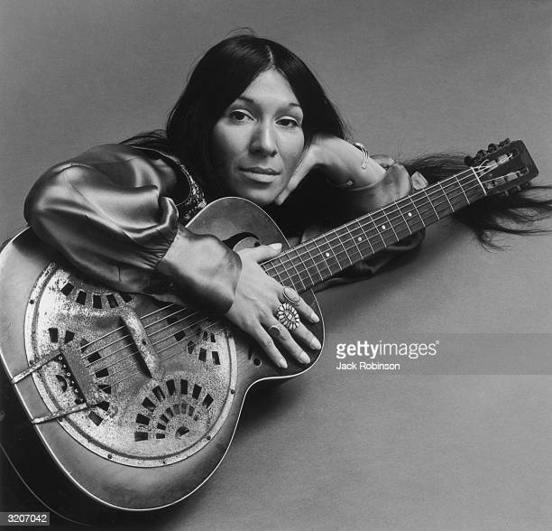 Portrait of Canadian musician Buffy St Marie lying on the floor holding her guitar her head resting on her palm She is wearing a long sleeved satin...