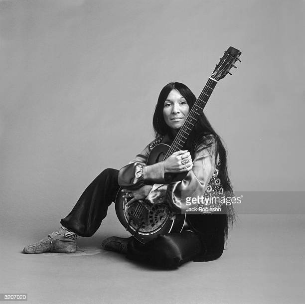 Portrait of Canadian musician Buffy St Marie sitting on the floor and holding her guitar She is wearing traditional Native American leather shoes...