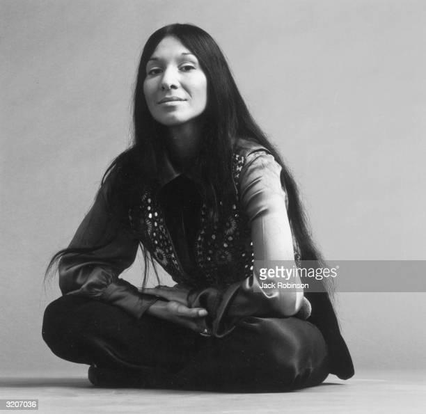 Portrait of Canadian musician Buffy St Marie sitting crosslegged on the floor with her hands together She wears black pants a satin longsleeved shirt...