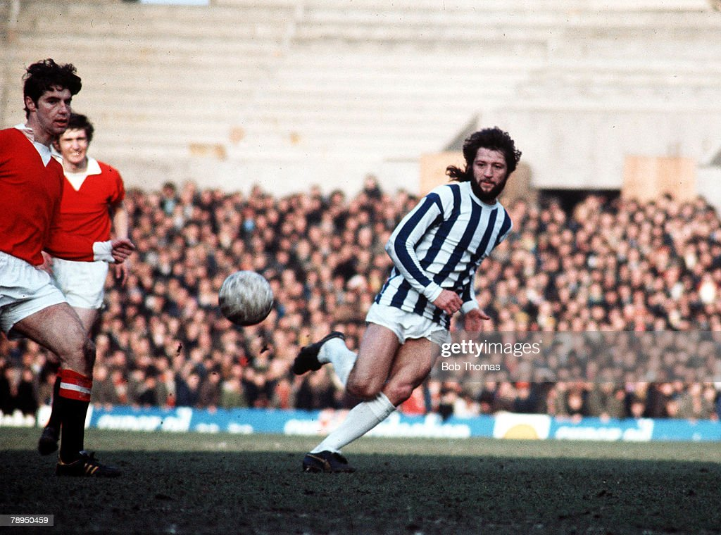 11th March 1972. Old Trafford, Manchester. Manchester United v Huddersfield Town. Huddersfield's Frank Worthington crosses the ball past Manchester United's Martin Buchan. : News Photo