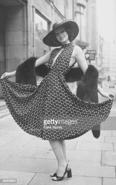 Model Marion Cameron in a Christian Dior navy crepe de chine dress with tiny floral print and slashed bodice Her broad brimmed hat of navy straw is...