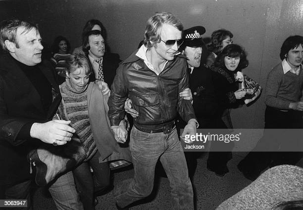 American actor and singer David Soul and his girlfriend the actress Lynne Martya being ushered through Heathrow Airport after his arrival