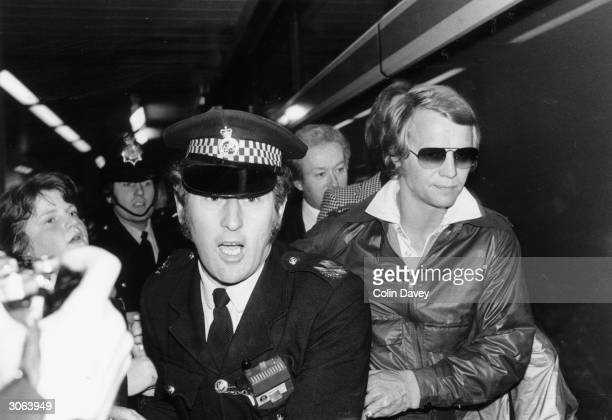 American actor and singer David Soul being ushered through Heathrow Airport after his arrival