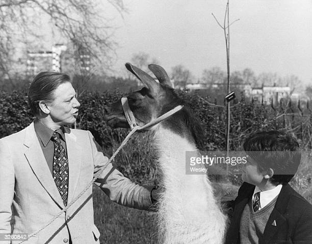 British naturalist and broadcaster David Attenborough shows Charlie the Llama to schoolboy Patrick Flynn the millionth child to attend London Zoo's...