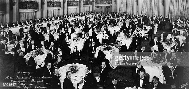 Interior view of formally dressed men and women seated at tables during the first organizational meeting of the Academy of Motion Picture Arts and...