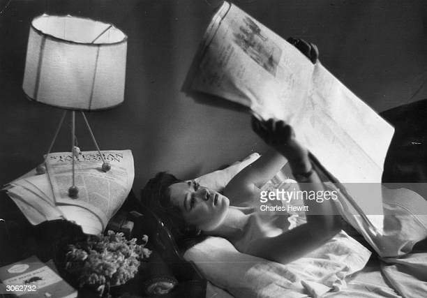 Secretary Bronwen HamiltonJenkins reads in bed in her Battersea south London flat Original Publication Picture Post 8808 Girl On Her Own unpub