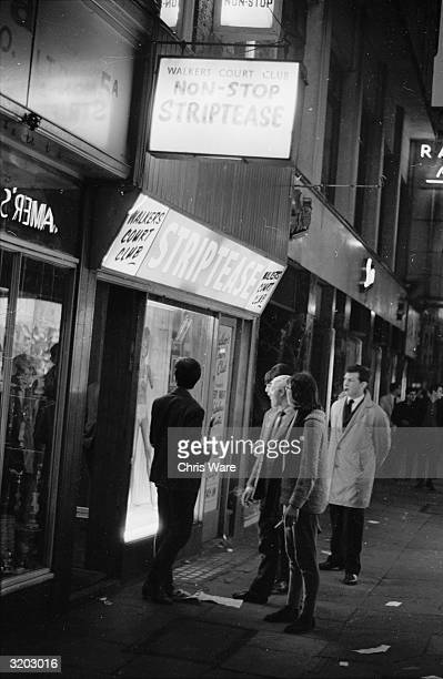 A group of people peer into the window of a club offering 'nonstop striptease' in Walkers Court in Soho London