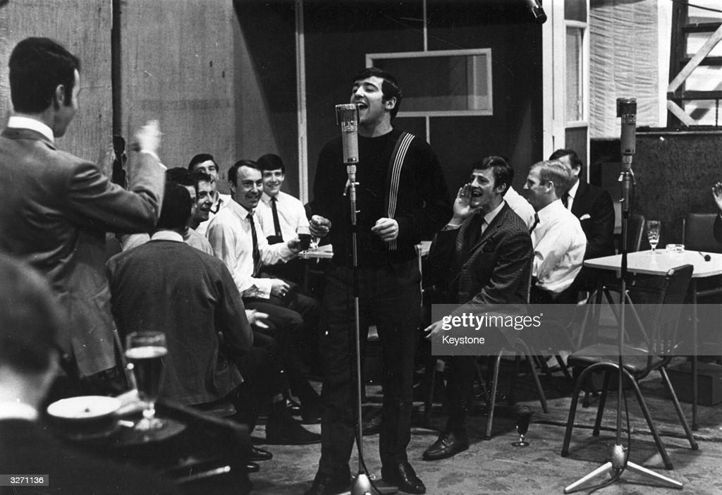 EMI recording producer Norman Smith conducts Terry Venables of Tottenham Hotspur Football Club, as his team-mates, amongst them Jimmy Greaves, watch him sing a solo during the recording of the team's FA Cup Final song.