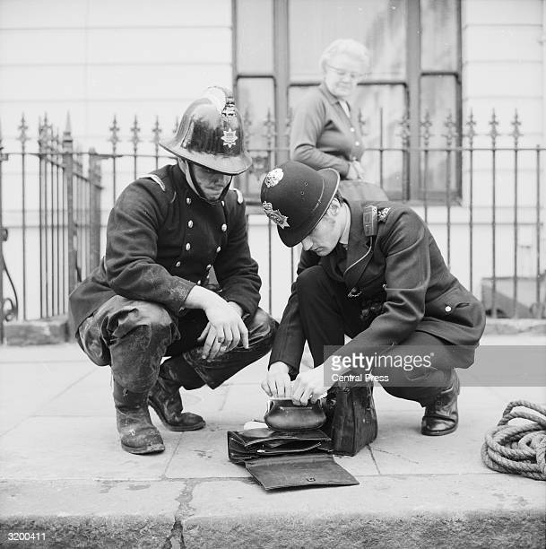 A firefighter and policeman search through the contents of handbags found in the New Langham Hotel in Bayswater London which was the scene of a...