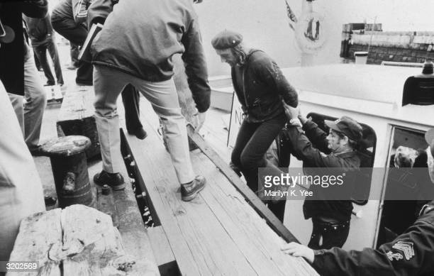 Political activist Edwin Drummond is led in handcuffs from a police launch boat Battery Park New York City Drummond and Stephen Rutherford were...