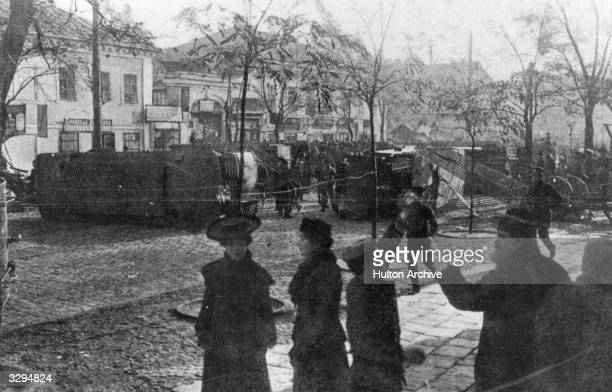 The locals view with consternation the disfigurement of Niejinskaya Street in Odessa. Revolutionaries have used overturned trams, carts, and iron...