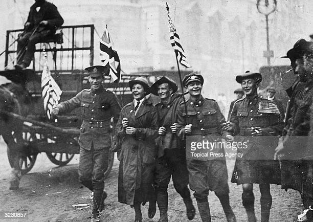 A group of soldiers including a Scot an Australian and a member of the WAAC running down the Strand in London on Armistice Day