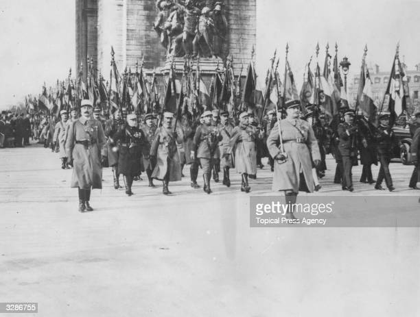 French flag bearers marching through the Arc de Triomphe, Paris, on Armistice Day.