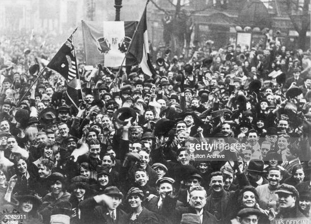 Happy crowd of Parisians wave their hats and flags during a celebration of the end of World War I on Armistice Day, Paris, France.