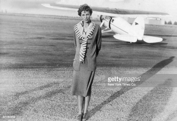 Fulllength image of American aviator Amelia Earhart standing on an airstrip in front of her White Lockeed Vega Monoplane in which she broke a speed...