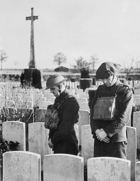 Two members of the BEF bow their heads in observance of the twominute silence at a cemetery in France This tradition commemorates those who died in...