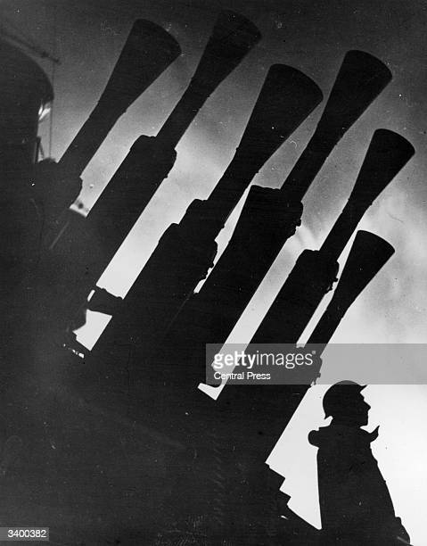 Gunner stands silhouetted at dusk with the guns of Britain's latest battleship HMS Prince Of Wales.