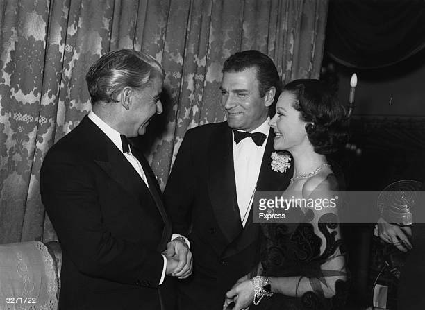 Sir Laurence Olivier and his wife Lady Olivier meet with Emlyn Williams at a function in London