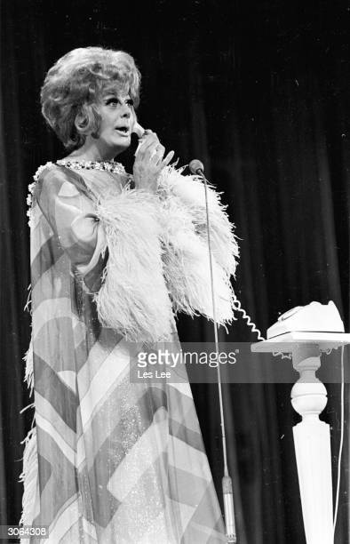 Drag artist Danny La Rue answers the phone as part of his act in A Royal Command Performance London Palladium