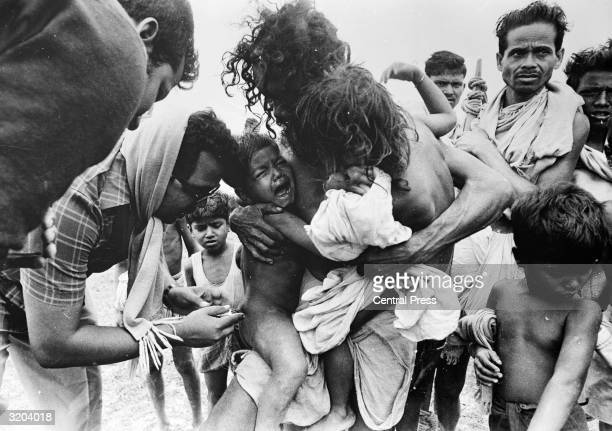 A young boy receives a vital injection to vaccinate him against the growing cholera epidemic which has arisen in the wake of a devastating cyclone in...