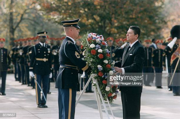 US President Ronald Reagan stands facing an American uniformed serviceman laying a wreath at the Tomb of the Unknown Soldier Arlington National...