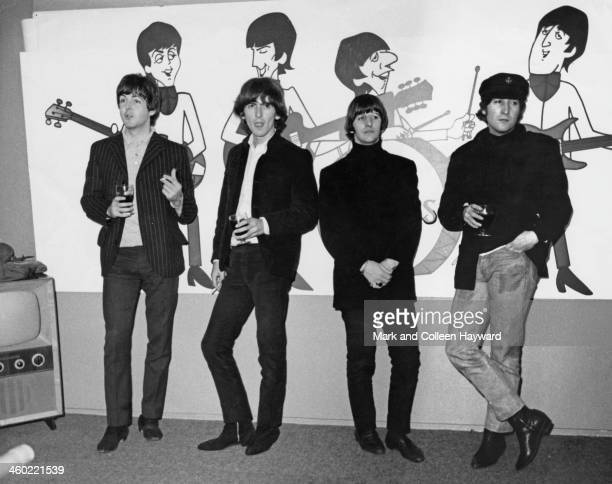 The Beatles pose in front of animated cartoons of themselves in London on 11th November 1964 From left to right Paul McCartney George Harrison Ringo...