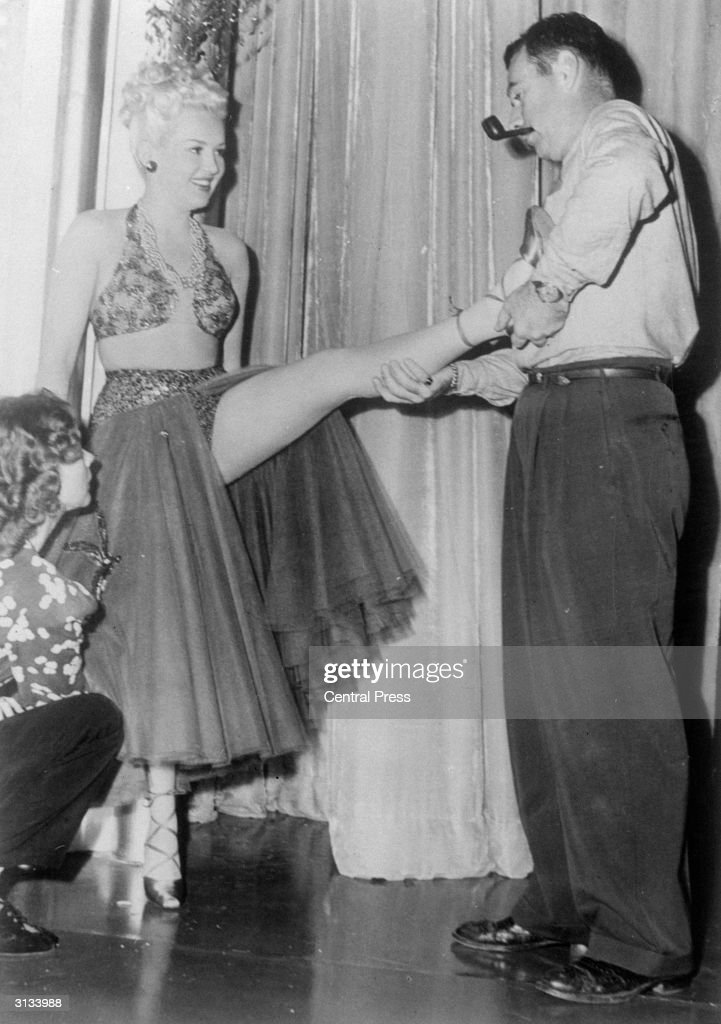 Kenny Williams, the dance director at the 20th Century Fox studios, relieves a touch of cramp in one of Betty Grable's famous legs. Ms Grable (1916 - 1973) is wearing an exotic costume for a scene in her current film 'The Dolly Sisters'.