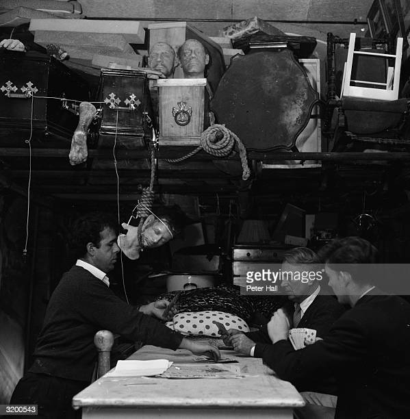 Studio technicians calmly play a game of cards ignoring the severed head swinging from a hangman's rope They are taking a break during the filming of...