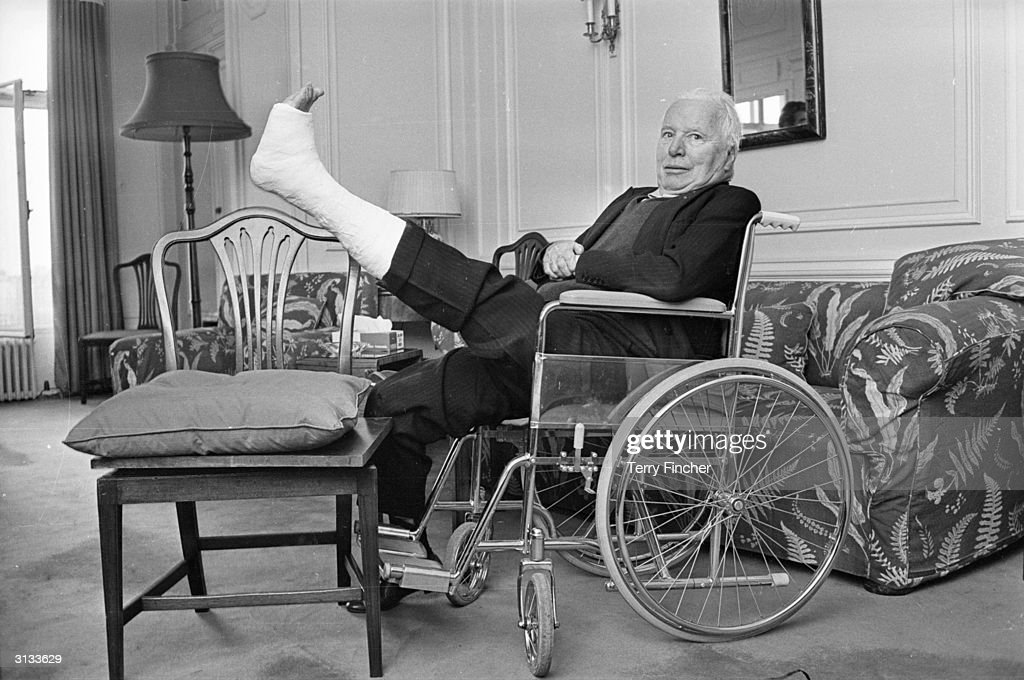 British born actor, comedian and director Charlie Chaplin with his leg in plaster after breaking a bone in his foot.