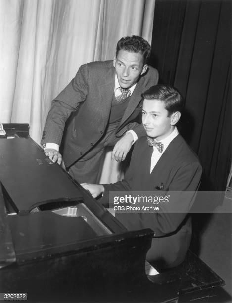 American singer Frank Sinatra leans next to composer and pianist Andre Previn while Previn plays piano on 'The Frank Sinatra Show' California Previn...