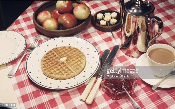 A plate of buttered waffles made in an Easywork waffle iron served with strawberry jam a cup of tea and a bowl of apples