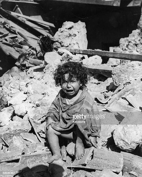 A small child sits crying amongst the rubble in Orleanville Algeria following an earthquake which killed 1100 people
