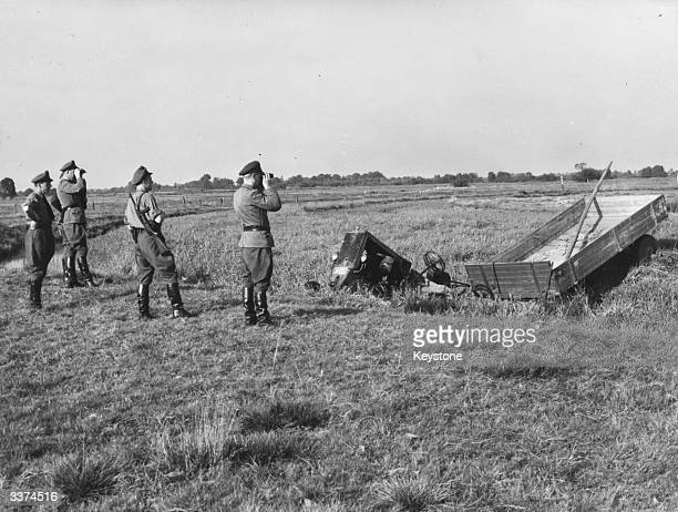 German officers scanning a field in West Germany for a man who escaped from the DDR by driving his tractor and trailer into the river which separates...