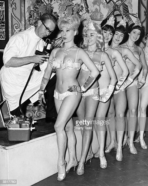 Windmill Theatre chorus girls being inoculated against influenza. The method being used is 'Influvac' which uses a jet spray instead of a needle.